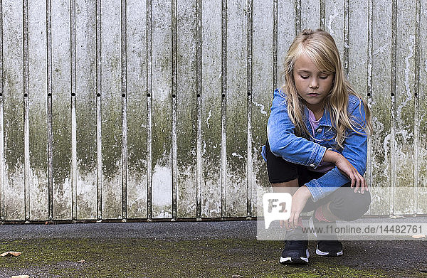 Portrait of serious blond girl crouching in front of wooden wall