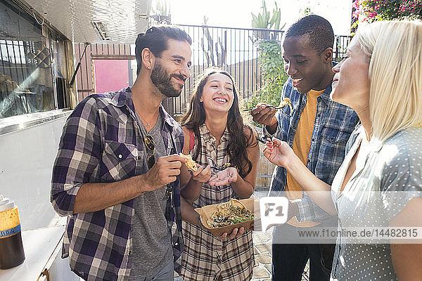 Glückliche Freunde teilen Essen zum Mitnehmen im Freien
