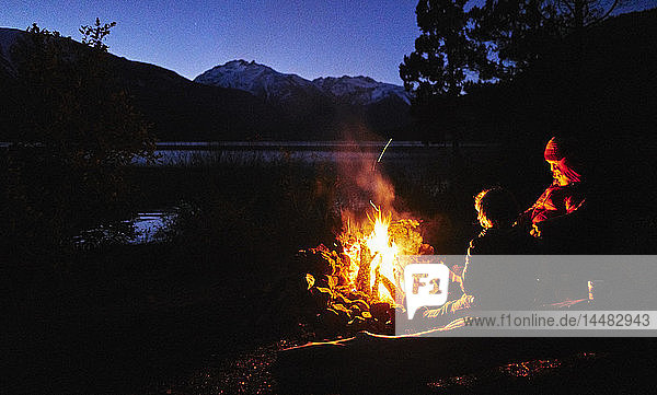 Argentina  Patagonia  Lago Futalaufquen  mother with sons at camp fire at night