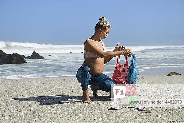 Schwangere Frau reinigt den Strand von Plastikmüll