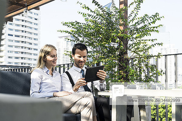 Smiling business colleagues on city terrace looking at tablet