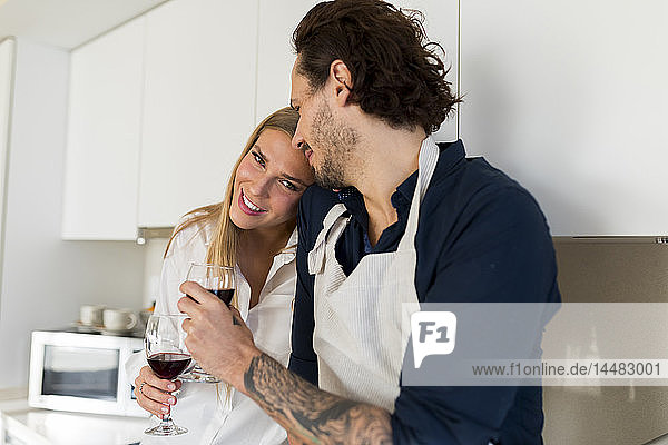 Liebespaar trinkt Rotwein in der Küche