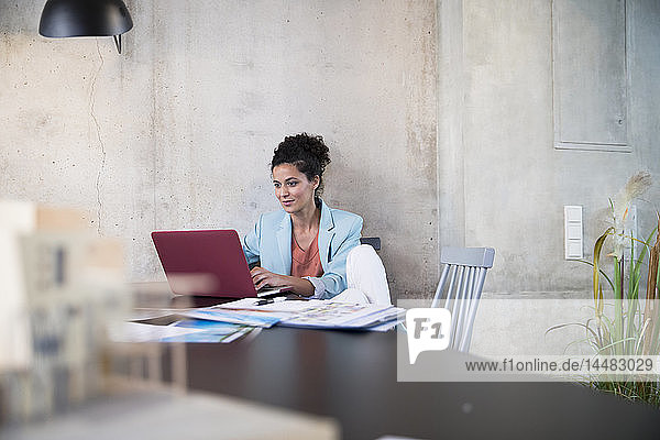 Businesswoman sitting at table in a loft using laptop