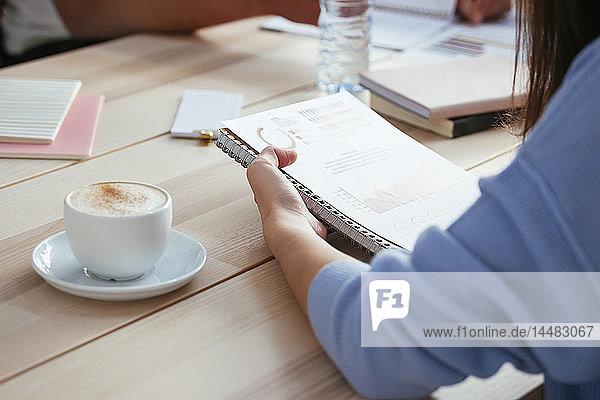 Frau arbeitet an Papier am Schreibtisch im Büro
