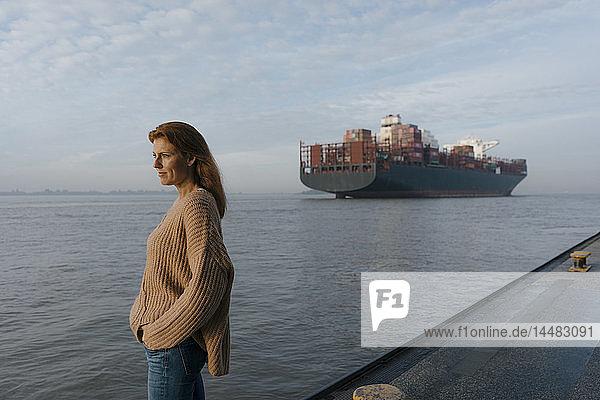 Deutschland  Hamburg  Frau auf der Pier am Elbufer stehend mit Containerschiff im Hintergrund
