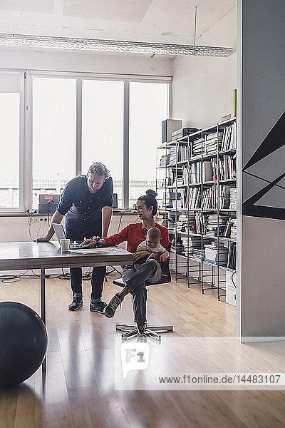 Berufstätige Mutter mit Baby auf dem Schoß  im Büro sitzend  mit Laptop