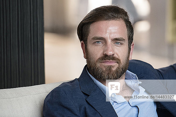 Businessman sitting on sofa in hotel lobby
