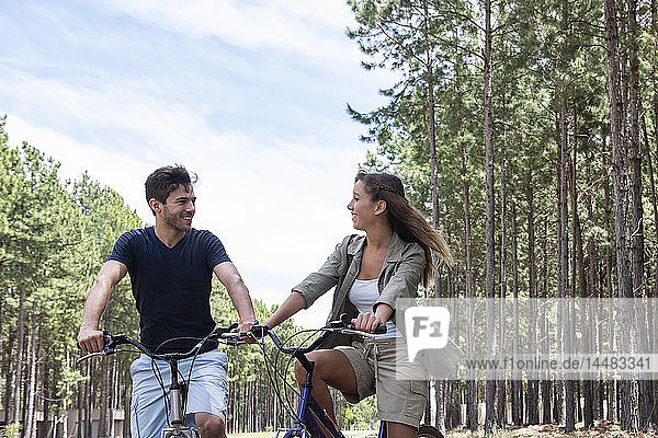 Young couple looking at each other while resting on bicycles