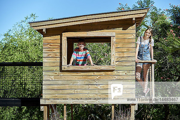 Boy and teenage girl standing in a log cabin