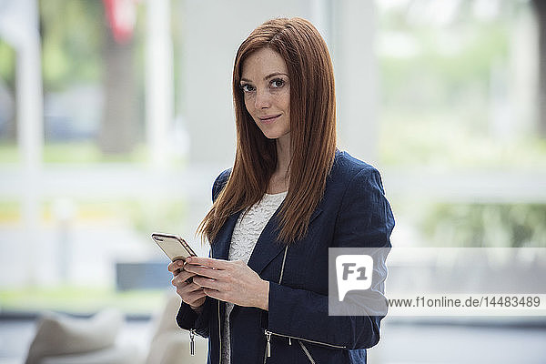 Woman holding smart phone in hotel lobby