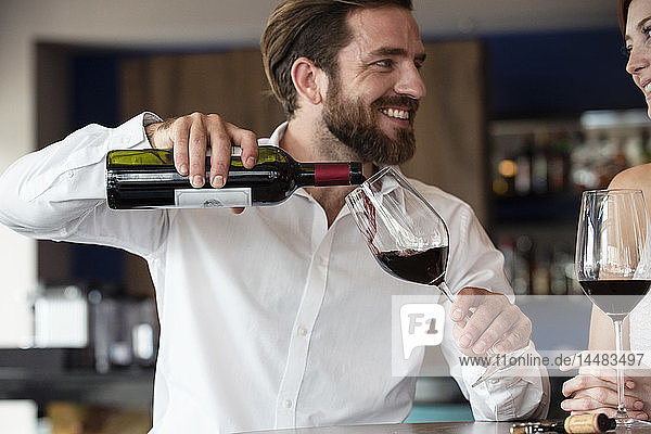 Mid adult man pouring red wine in glass