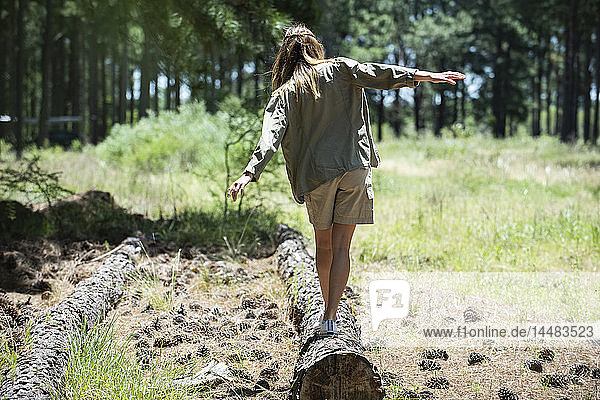 Young woman walking on log in forest