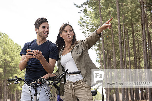 Young couple standing with bicycles in pine forest