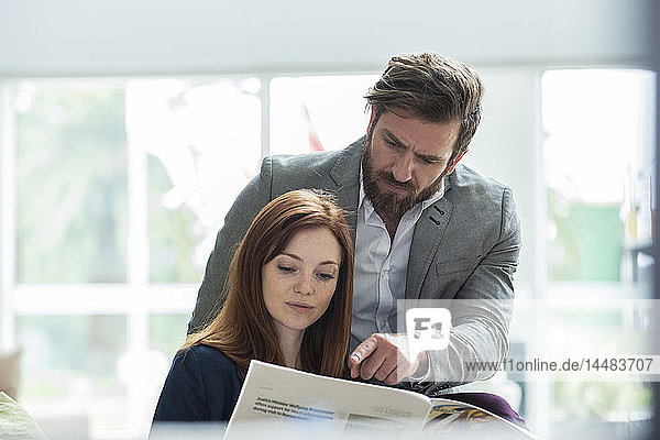 Business people reading newspaper in hotel
