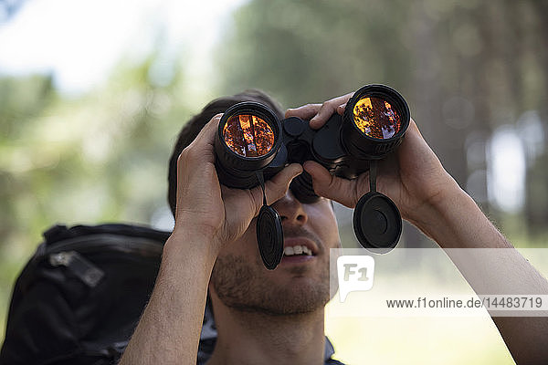 Young man looking through binoculars in forest