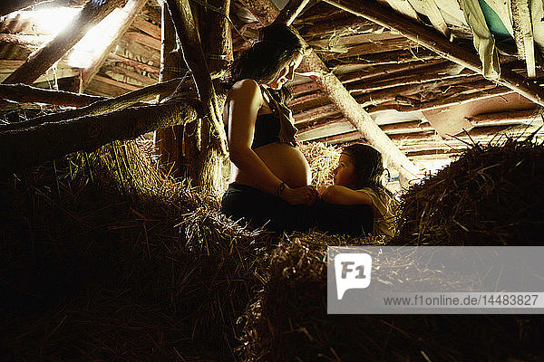Pregnant mother and daughter in rural hay loft