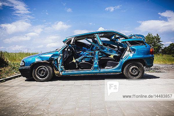 Mangled blue car in sunny parking lot