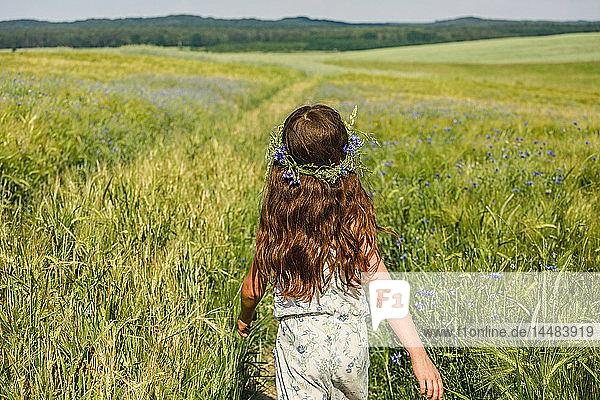 Girl with flowers in hair walking in sunny  idyllic green field
