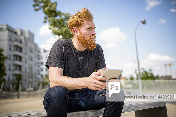 Hipster man with beard using digital tablet on urban bench