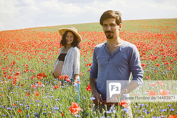 Portrait smiling pregnant couple in sunny  idyllic rural red poppy field