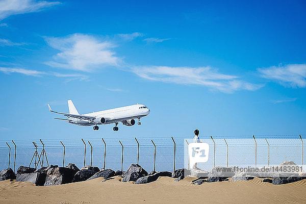 Boy on beach watching airplane flying low in blue sky near Lanzarote Airport  Spain