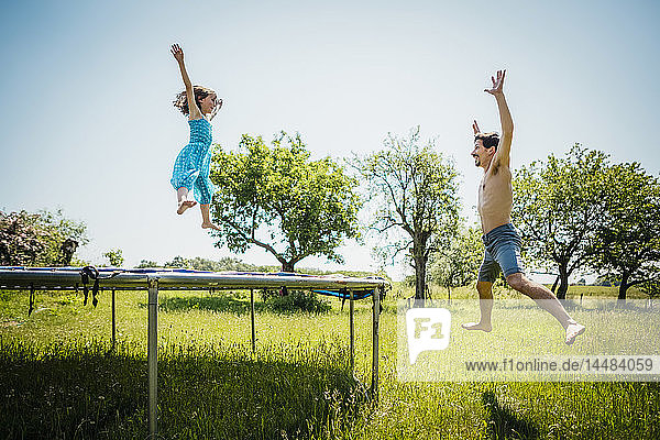 Playful father and daughter jumping on trampoline in sunny summer back yard