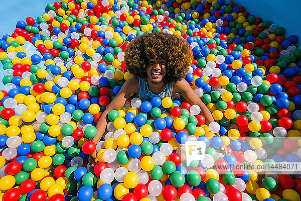 Portrait exuberant young man playing in multicolor ball pool