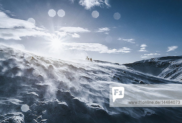 People walking along sunny  windy  snow covered mountain  Reykjadalur  Iceland