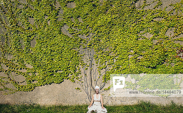 Portrait serene woman meditating at wall overgrown with ivy