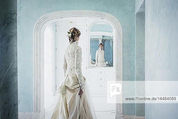 Elegant bride in lace wedding dress at mirror