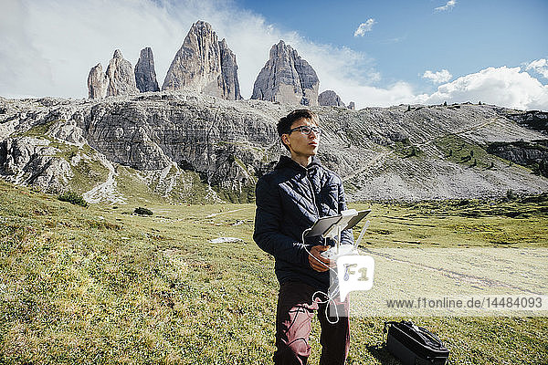 Boy with digital tablet and joystick controlling drone in sunny Drei Zinnen Nature Park  South Tyrol