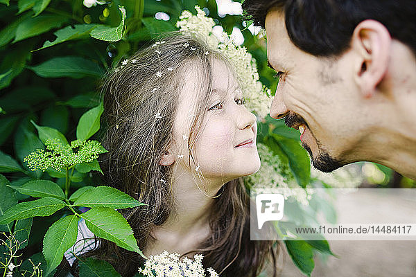Affectionate father and daughter at flowering bush