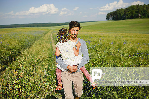 Portrait father carrying daughter in sunny  idyllic rural field