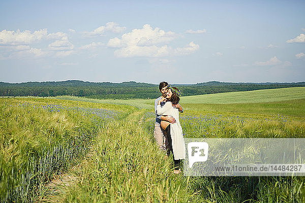 Affectionate pregnant couple hugging in sunny  idyllic rural green field