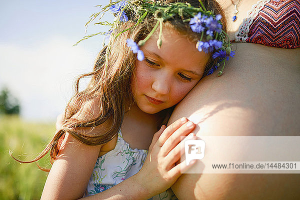 Serene girl with flowers in hair leaning on pregnant mothers stomach