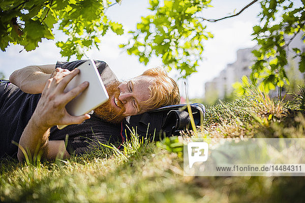 Smiling man with beard using digital tablet in sunny park