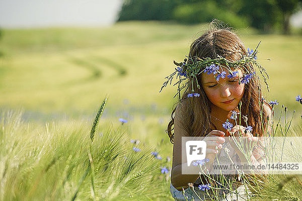 Curious girl with wildflowers in hair in sunny  rural wheat field