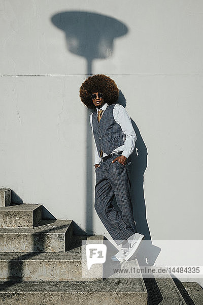 Portrait confident  cool  well-dressed young man with afro on urban steps