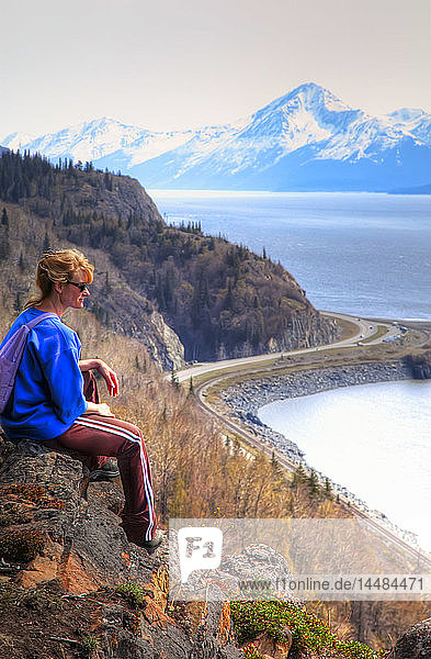 Woman sits on ridge overlooking Turnagain Arm with Seward Highway and Chugach Mountains in the background  HDR image