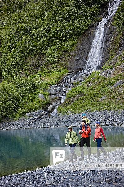 Group of people walking along the shoreline near a waterfall  Shoup Bay State Marine Park  Prince William Sound  Southcentral Alaska  Summer