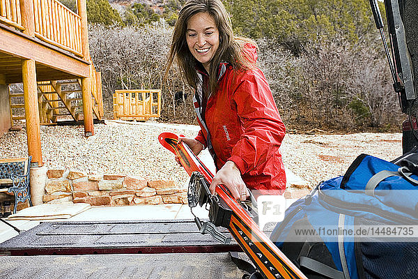 Woman loading backcountry skis into the back of pickup truck Cedar City Utah Winter