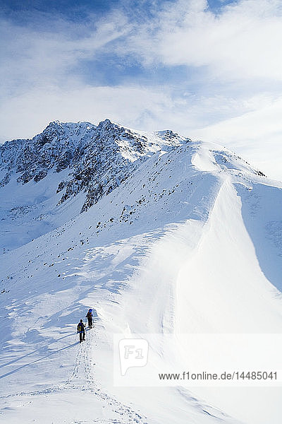 Two snowshoers ascend a ridge above Eagle River in Chugach State Park. Winter in Southcentral Alaska.
