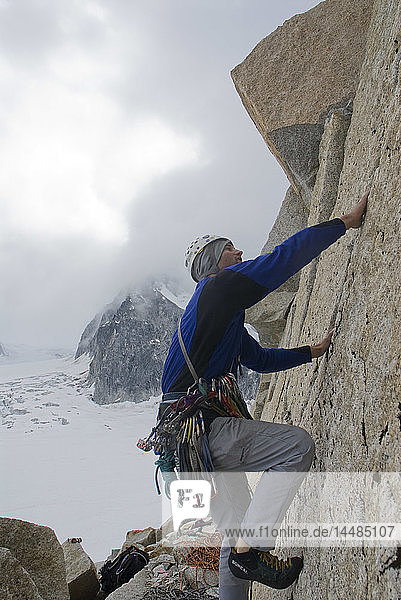 Rock climber on granite wall above Pika Glacier in *Little Switzerland* of Denali National Park  Alaska