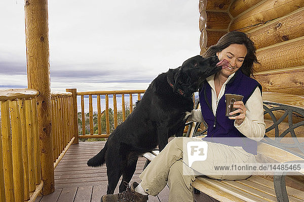 Friendly dog kisses owner while relaxing on deck of log home Utah Winter
