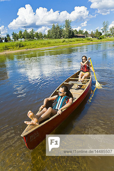 Young women paddle downstream in a tandem canoe on the Chena river in Fairbanks  Alaska during Summer