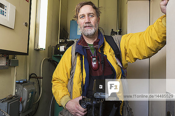 Official Iditarod photographer waiting for an elevator in a parking garage during the 2014 Iditarod  Anchorage  Southcentral Alaska