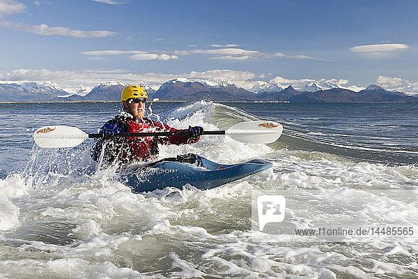 Man Kayak Surfing waves on Katchemak Bay near Homer Kenai Peninsula Alaska Autumn