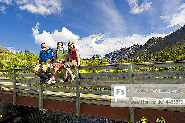 Family sitting on the railing of a bridge along the boardwalk of the Middle Fork Loop Trail in the Glen Alps area of Chugach State Park  Southcentral Alaska