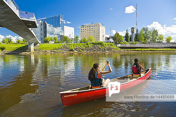 Young women paddle downstream in a tandem canoe on the Chena river past downtown Fairbanks  Alaska during Summer