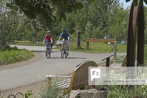 Young Man & Woman Bike on Anchorage Coastal Trail AK SC Summer